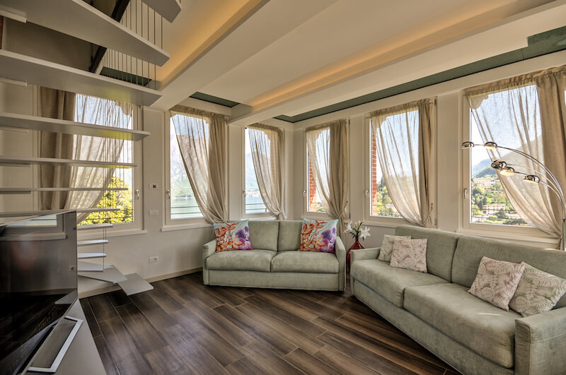 beautiful light living room with sofa bed and windows with lake view