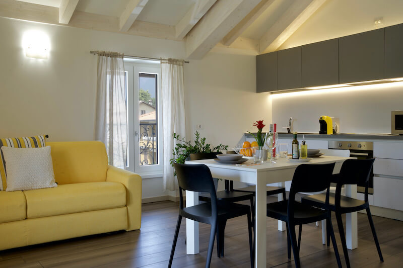 modern holiday apartment with sofa bed, table and chairs and equipped kitchen