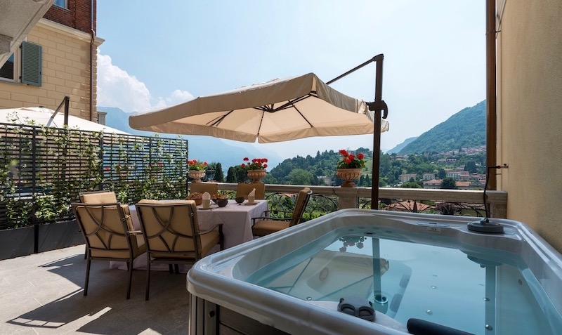 Terrace with jacuzzi, table and chairs and umbrella