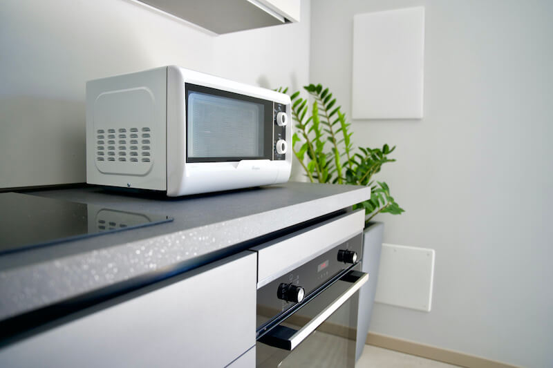equipped kitchen with oven and microwave