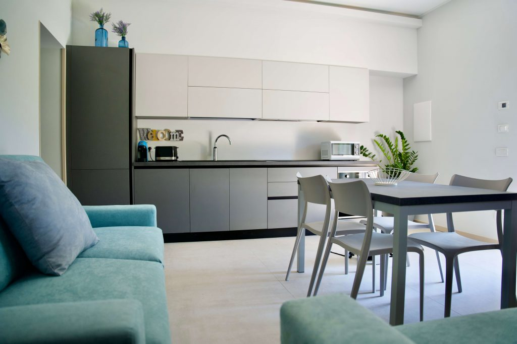 modern apartment with equipped kitchen, coffee machine, microwave, table and chiars and sofa bed